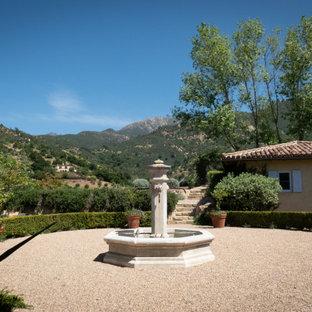 Photo of a large mediterranean full sun courtyard gravel landscaping in Santa Barbara.