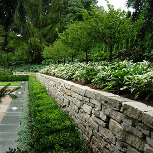 Cette image montre un jardin traditionnel avec un mur de soutènement et une exposition partiellement ombragée.