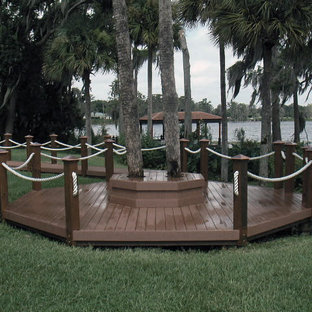 Design ideas for a large tropical partial sun backyard landscaping in Orlando with decking.
