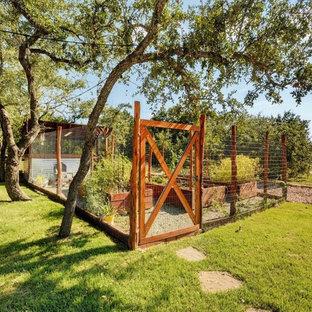 Exempel på en mellanstor rustik formell trädgård i full sol längs med huset på våren, med en köksträdgård och grus