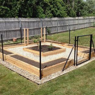 Inspiration för små formella trädgårdar i full sol längs med huset på sommaren, med en köksträdgård och grus