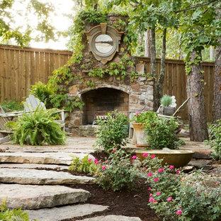 Aménagement d'un jardin classique avec des pavés en pierre naturelle et une cheminée.