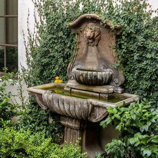 Cette image montre un très grand jardin à la française arrière méditerranéen avec une entrée ou une allée de jardin, une exposition ensoleillée et un gravier de granite.