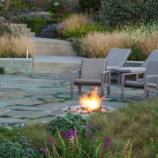 Réalisation d'un jardin marin l'été avec un foyer extérieur, une exposition ensoleillée, une pente, une colline ou un talus et des pavés en pierre naturelle.