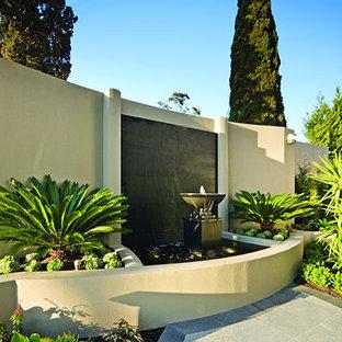 Modelo de jardín mediterráneo, de tamaño medio, en patio trasero, con fuente y adoquines de piedra natural