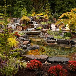 Photo of a rustic backyard stone waterfall in Seattle.
