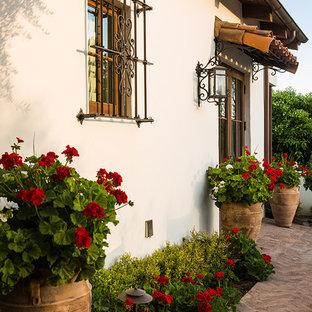 Foto de jardín de secano, mediterráneo, de tamaño medio, en primavera, en patio trasero, con jardín de macetas y exposición parcial al sol