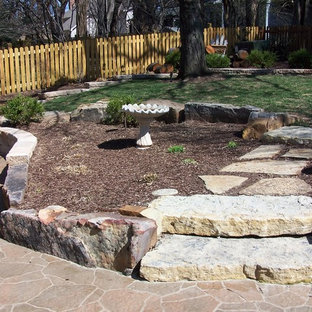Inspiration for a mid-sized traditional partial sun backyard stone retaining wall landscape in Kansas City.