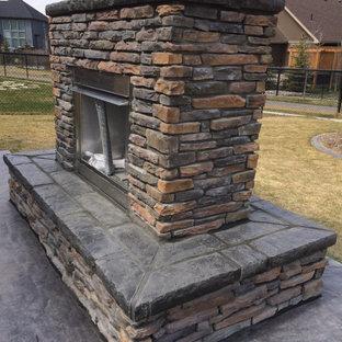 Mittelgroßer Garten hinter dem Haus mit Kamin und Betonplatten in Calgary