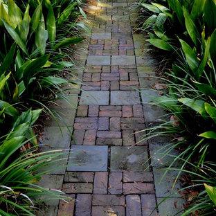 Inspiration för mellanstora exotiska trädgårdar framför huset, med marksten i tegel och en trädgårdsgång