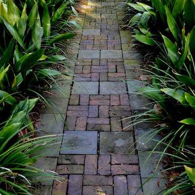 This is an example of a mid-sized tropical front yard brick garden path in Atlanta.