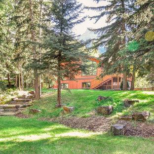 Großer, Halbschattiger Moderner Hanggarten Im Frühling Mit Auffahrt,  Gartenweg Und Natursteinplatten In Calgary