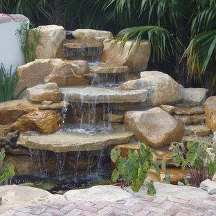 Modelo de jardín clásico, grande, en patio trasero, con fuente y adoquines de piedra natural
