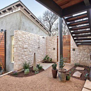 This is an example of a large farmhouse partial sun and drought-tolerant courtyard gravel landscaping in Austin.