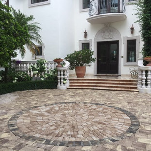 Inspiration for a large mediterranean full sun front yard concrete paver driveway in Miami.