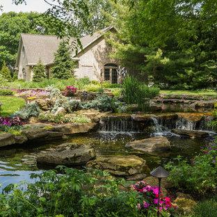 На фото: огромный весенний садовый фонтан на склоне в стиле кантри с