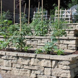 На фото: солнечный участок и сад среднего размера на склоне в стиле кантри с растениями в контейнерах, хорошей освещенностью и мульчированием с