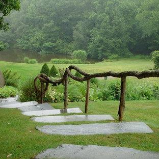 Inredning av en rustik bakgård, med en damm och naturstensplattor