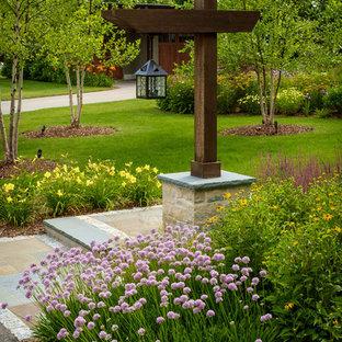 Idée de décoration pour un grand jardin avant tradition avec des pavés en pierre naturelle et un massif de fleurs.