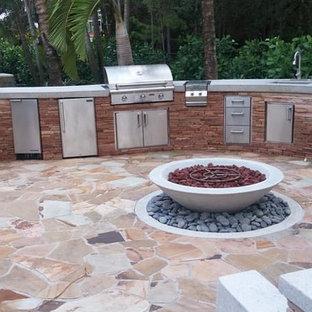 Idéer för att renovera en stor tropisk bakgård i delvis sol, med en öppen spis och naturstensplattor