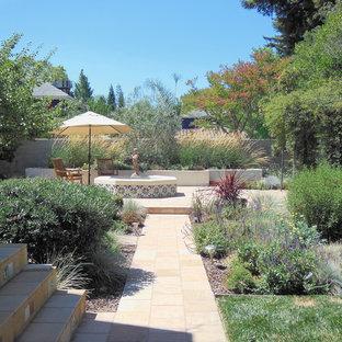 Exempel på en stor medelhavsstil trädgård i full sol på våren, med naturstensplattor och en fontän