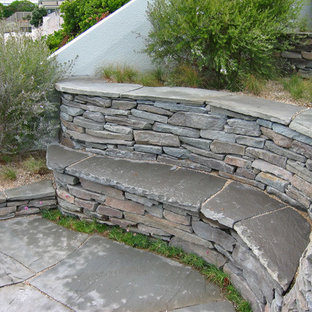 Photo of a mid-sized beach style drought-tolerant and full sun hillside stone retaining wall landscape in San Francisco for winter.
