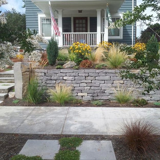 This is an example of a mid-sized traditional partial sun front yard stone landscaping in Portland.
