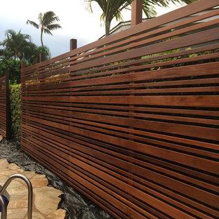 Bild på en mellanstor tropisk bakgård i full sol, med naturstensplattor