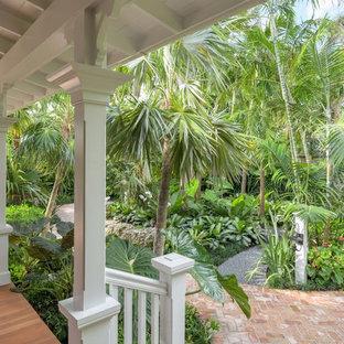 Inspiration för en mellanstor tropisk trädgård i delvis sol framför huset, med marksten i tegel