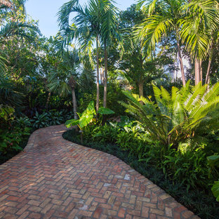 Inspiration for a mid-sized tropical partial sun front yard brick landscaping in Miami.
