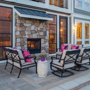 Mittelgroßer Moderner Garten hinter dem Haus mit Kamin, direkter Sonneneinstrahlung und Betonplatten in Minneapolis