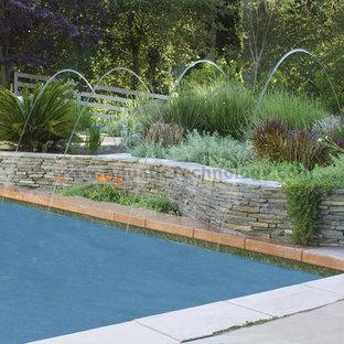 Foto de jardín francés, mediterráneo, grande, en patio trasero, con fuente y adoquines de piedra natural