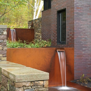 Photo of a mid-sized contemporary backyard full sun garden in Burlington with a water feature and natural stone pavers.