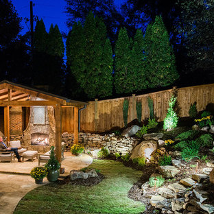 Design ideas for a large craftsman partial sun backyard stone landscaping in Atlanta with a fire pit.