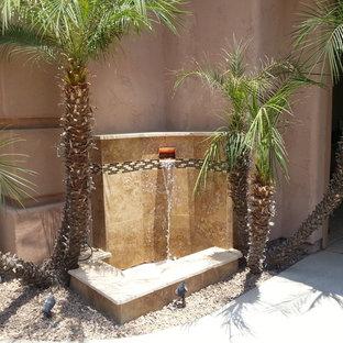 Inspiration för en liten funkis trädgård i full sol, med en fontän