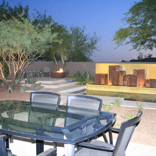 This is an example of a mid-sized contemporary drought-tolerant and full sun backyard mulch landscaping in Phoenix.