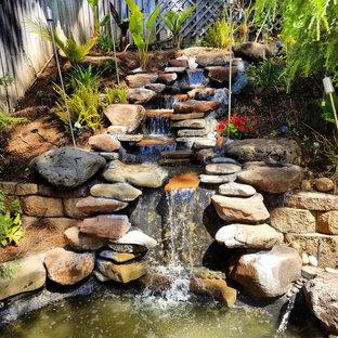 Ejemplo de jardín de estilo zen, de tamaño medio, en patio trasero, con fuente, exposición parcial al sol y adoquines de piedra natural