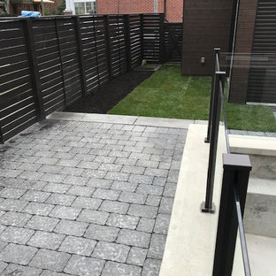 Inspiration for a small contemporary privacy and partial sun backyard concrete paver landscaping in Toronto.
