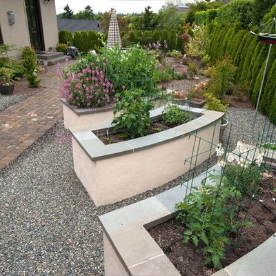 This is an example of a large traditional backyard stone landscaping in Seattle.