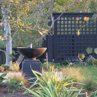 Foto på en eklektisk trädgård, med en fontän