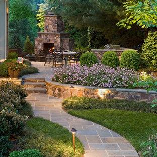 Réalisation d'un grand jardin arrière tradition avec des pavés en pierre naturelle et une cheminée.