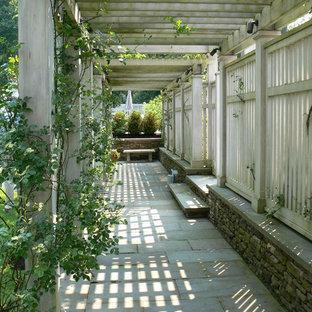 Esempio di un grande giardino formale chic esposto in pieno sole davanti casa in primavera con pavimentazioni in cemento e recinzione in legno