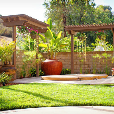 Photo of a mid-sized mediterranean full sun backyard stone and stone fence formal garden in San Diego for fall.