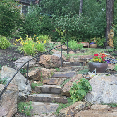 Design ideas for a mid-sized rustic hillside stone retaining wall landscape in Seattle.