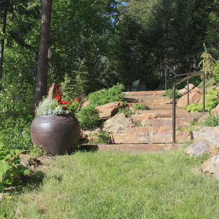 This is an example of a mid-sized rustic hillside stone landscaping in Seattle.