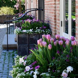 Пример оригинального дизайна: большой весенний участок и сад на переднем дворе в классическом стиле с растениями в контейнерах, полуденной тенью и покрытием из каменной брусчатки