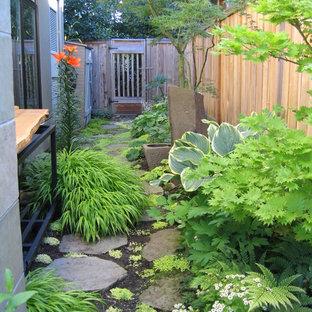 Modern inredning av en trädgård i skuggan längs med huset, med naturstensplattor