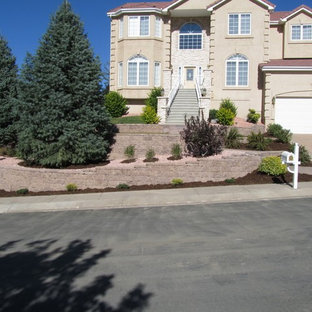 Photo of a mid-sized transitional full sun front yard stone landscaping in Denver.