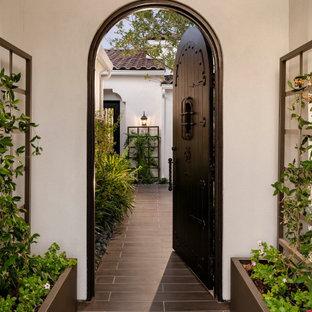Großer, Halbschattiger Moderner Garten im Sommer, hinter dem Haus mit Kamin, Betonplatten und Metallzaun in Phoenix