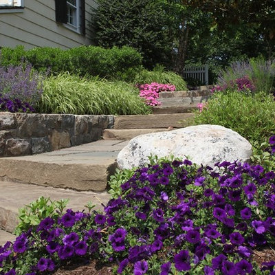Inspiration for a large traditional full sun backyard stone landscaping in New York.